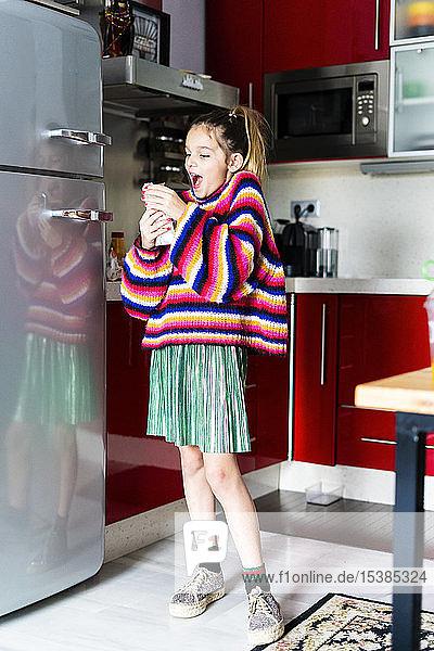 Aufgeregtes Mädchen in gestreiftem Pullover in der heimischen Küche beim Schokoladenessen