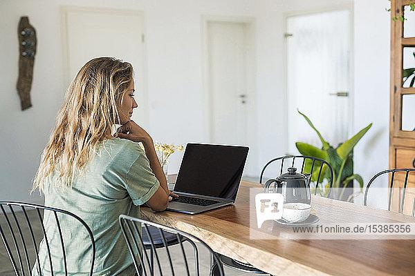 Frau benutzt Laptop auf dem Esstisch zu Hause