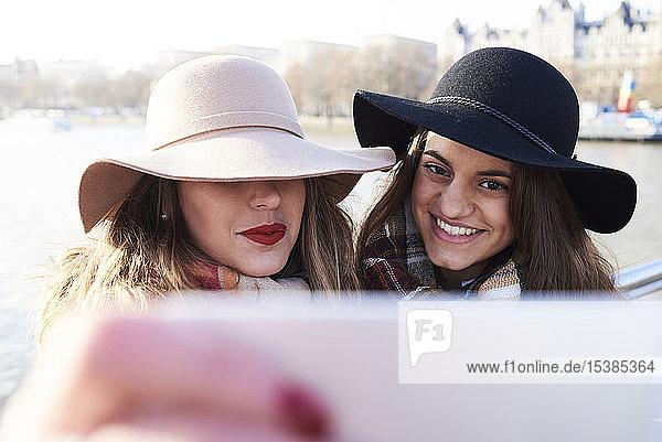 UK  London  two women wearing floppy hats taking a selfie on Millennium Bridge
