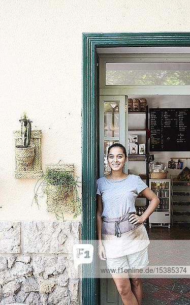 Porträt einer lächelnden Frau  die an der Eingangstür eines Cafés steht
