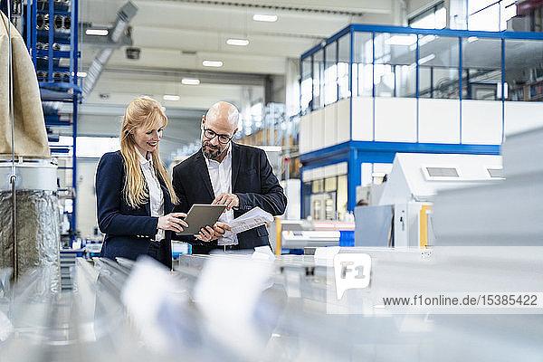 Geschäftsmann und Geschäftsfrau mit Tablette diskutieren in Fabrik