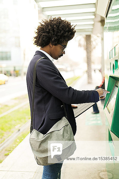 Spain  Barcelona  businessman using ticket machine at tram stop in the city