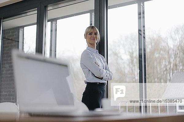 Erfolgreiche Geschäftsfrau im Konferenzraum  lächelnd  mit verschränkten Armen