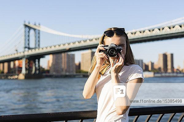 Junge Frau erkundet New York City  fotografiert an der Brooklyn Bridge