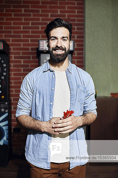 Portrait of smiling man holding darts