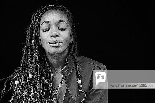 Portrait of woman with dreadlocks in front of black background