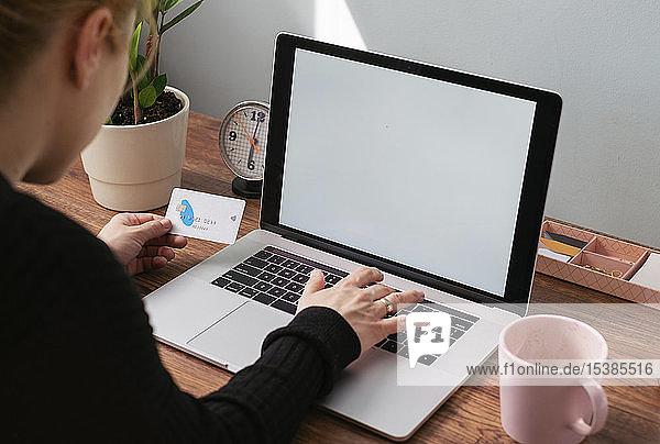 Frau benutzt Laptop und Kreditkarte für Online-Einkäufe  teilweise Ansicht