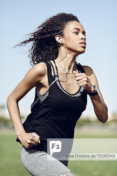 Sportliche junge Frau mit laufenden Kopfhörern