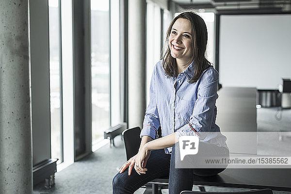 Lächelnde Geschäftsfrau sitzt im Büro am Konferenztisch