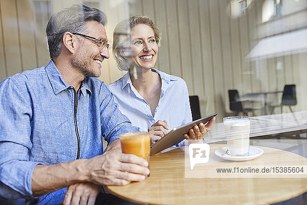 Glückliche Frau und Mann benutzen Tabletten in einem Café