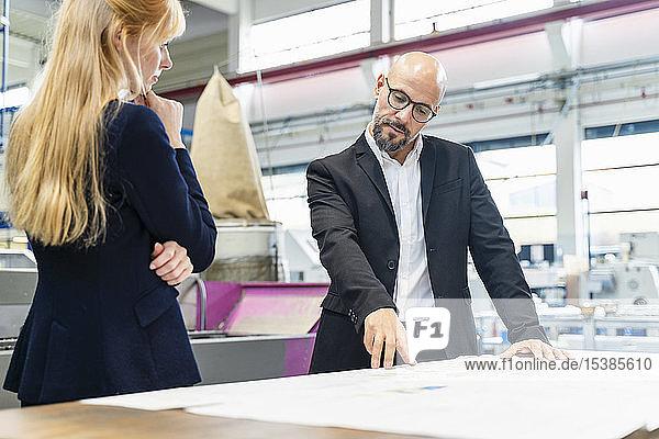 Geschäftsmann und Geschäftsfrau betrachten Plan auf dem Tisch in der Fabrik