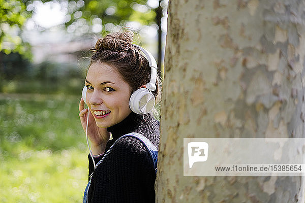 Young woman with headphones in a park