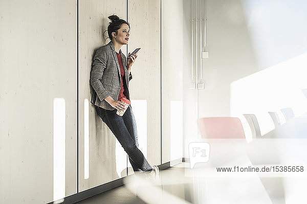 Businesswoman leaning against a wall in office using cell phone