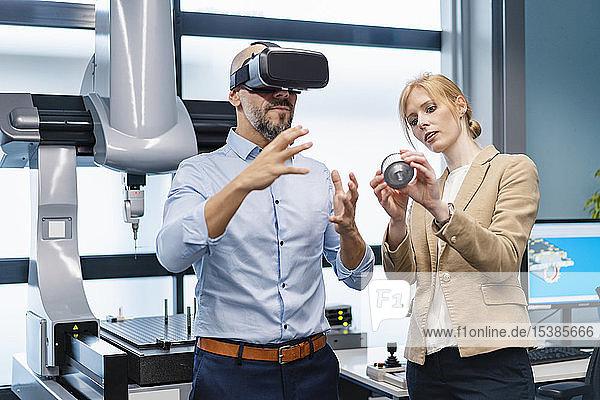 Geschäftsmann und Geschäftsfrau mitVR -Brille und Werkstück in der Fabrik