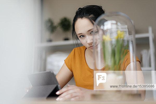 Junge Frau mit Tablette am Tisch  die eine Pflanze unter Glas betrachtet