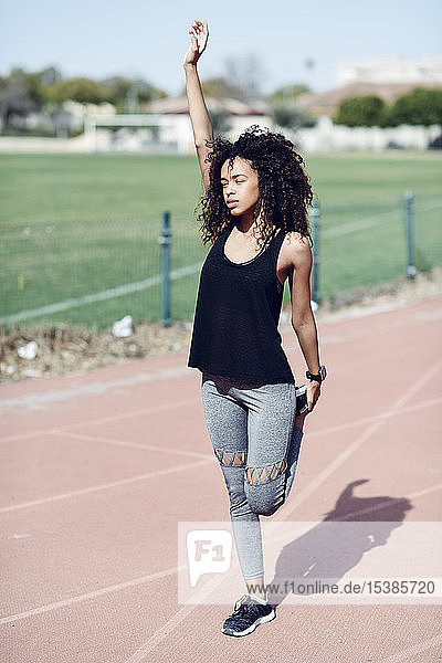 Sporty young woman stretching on tartan track