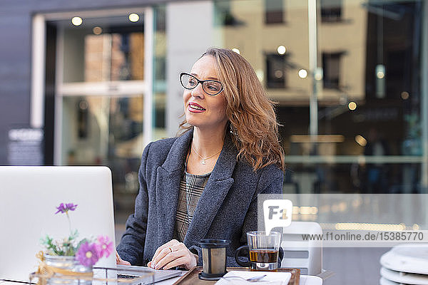 Reife Geschäftsfrau mit Laptop in einem Café im Freien