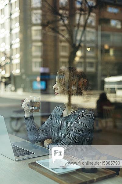 Reife Geschäftsfrau mit einem Laptop mit einem Glas Tee in einem Cafe