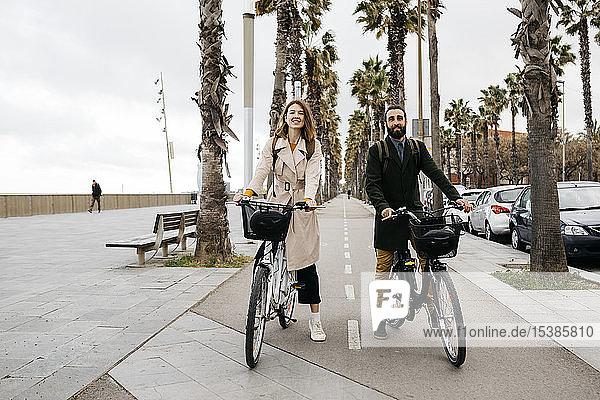 Porträt eines Paares mit E-Bikes auf einer Promenade