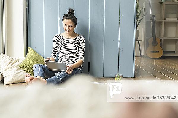 Frau  die zu Hause am Fenster sitzt und mit einem Laptop arbeitet