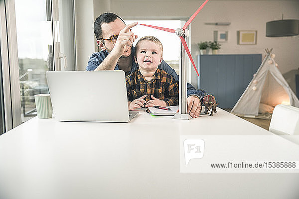Father and son at home with wind turbine model on table