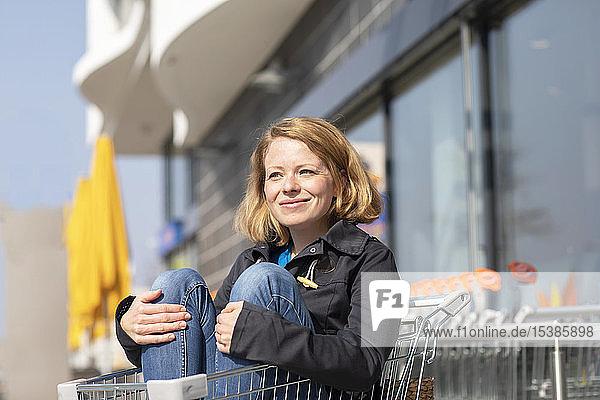 Porträt einer lächelnden Frau  die im Einkaufswagen vor dem Supermarkt sitzt