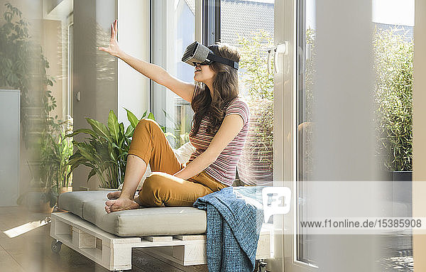 Young woman sitting at the window at home wearing VR glasses