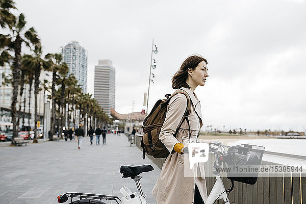 Woman with e-bike having a break on beach promenade