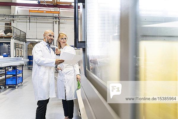 Zwei Techniker mit Laborkittel und Schutzbrille tragen Untersuchungsmaschine