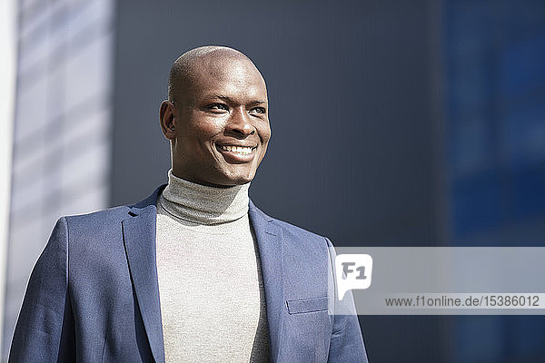 Portrait of smiling businessman wearing blue suit and turtleneck pullover