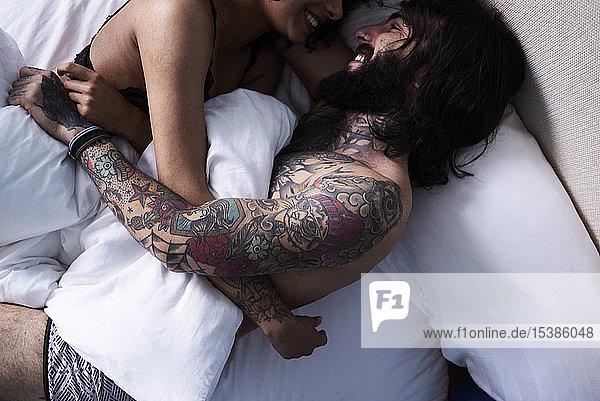 Glückliches  liebevolles  junges Paar liegt im Bett