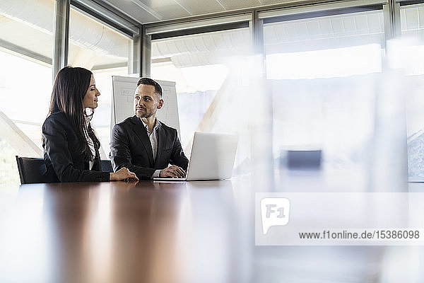 Geschäftsfrau und Geschäftsmann mit Laptop arbeiten im Büro