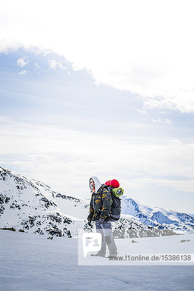 Junger Mann mit Rucksack  im Hintergrund schneebedeckte Berge