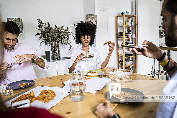 Freunde haben Spaß  essen Pizza  machen Smartphone-Fotos