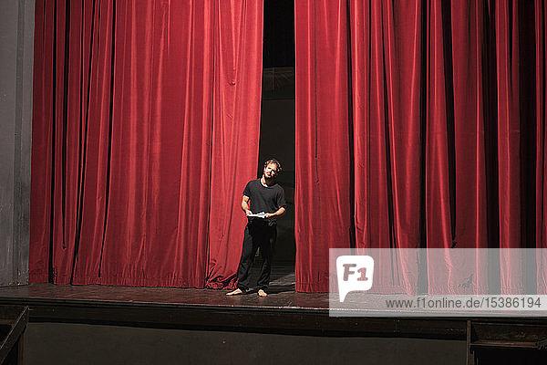Barfüssiger Schauspieler mit Drehbuch auf der Theaterbühne stehend Barfüssiger Schauspieler mit Drehbuch auf der Theaterbühne stehend