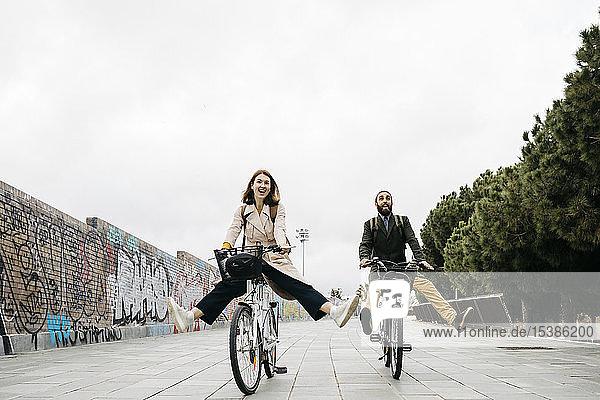 Sorgenfreies Paar fährt E-Bike auf einer Promenade