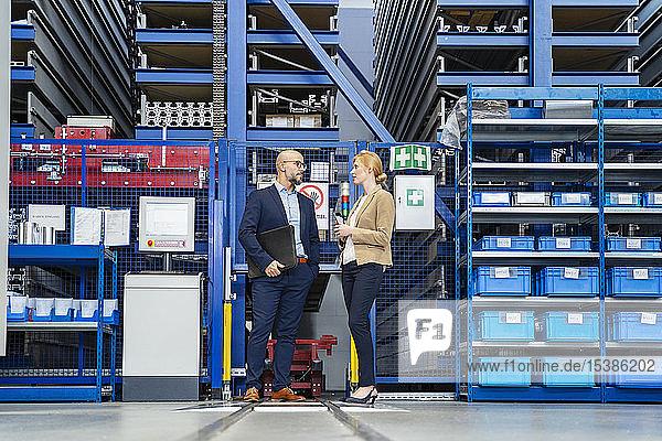 Geschäftsmann und Geschäftsfrau im Gespräch in der Fabrik