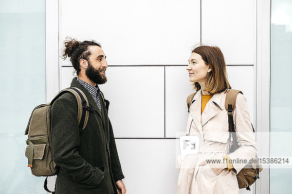 Man and woman talking at a building