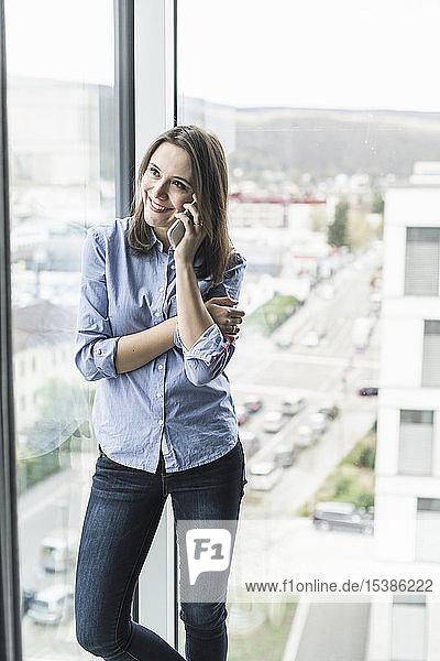 Lächelnde Geschäftsfrau am Handy  die im Büro am Fenster steht