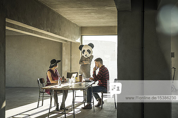 Woman with panda mask watching colleagues in office