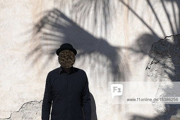 Morocco  Essaouira  man with obscured face wearing a bowler hat at a wall