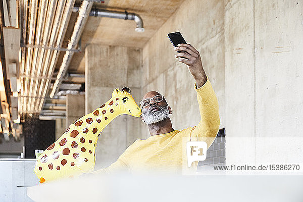Mature businessman sitting at desk in office with giraffe figurine taking a selfie