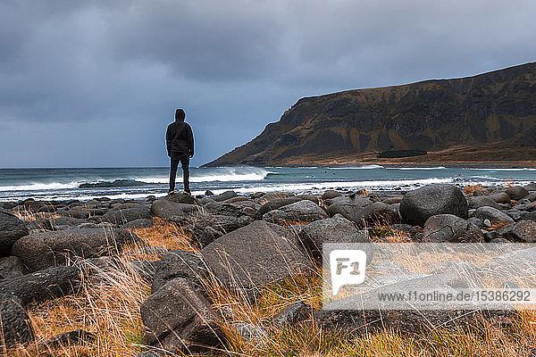 Norwegen  Lofoten-Inseln  Eggum  Rückenansicht des Mannes  der die Ansicht betrachtet
