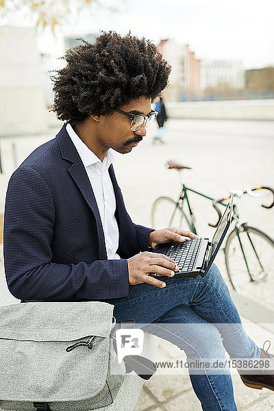 Spain  Barcelona  businessman with bicycle in the city sitting on bench using laptop