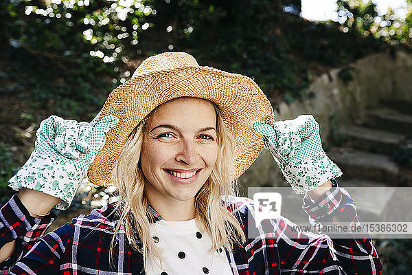 Young blond woman with straw hat and green gardening gloves