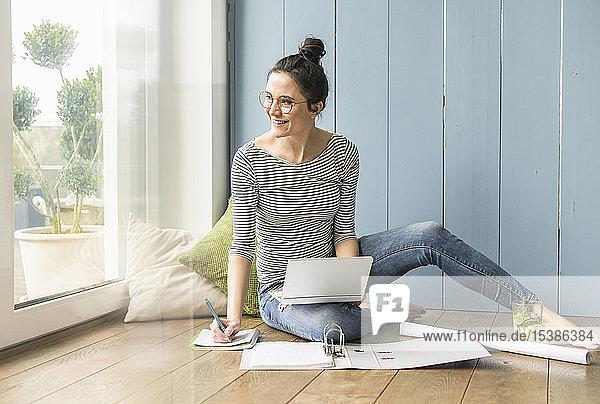 Lächelnde Frau sitzt zu Hause am Fenster und arbeitet mit Laptop und Dateiordner