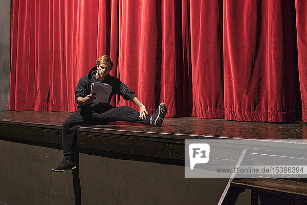 Schauspieler sitzt auf der Bühne des Theaters und studiert das Drehbuch Schauspieler sitzt auf der Bühne des Theaters und studiert das Drehbuch
