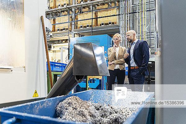 Geschäftsmann und Geschäftsfrau mit Schutzbrille an einer Maschine in einer Fabrik