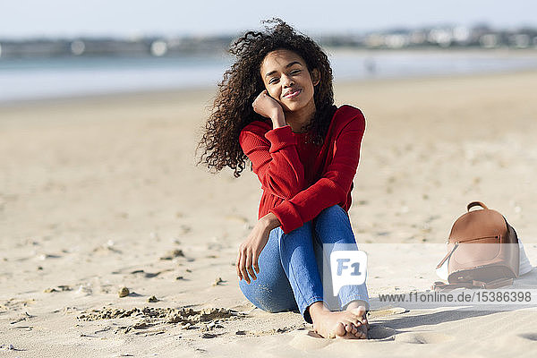 Portrait of smiling young woman sitting on the beach