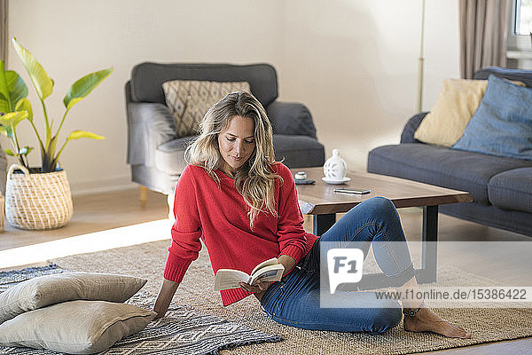 Woman sitting on the floor at home reading book